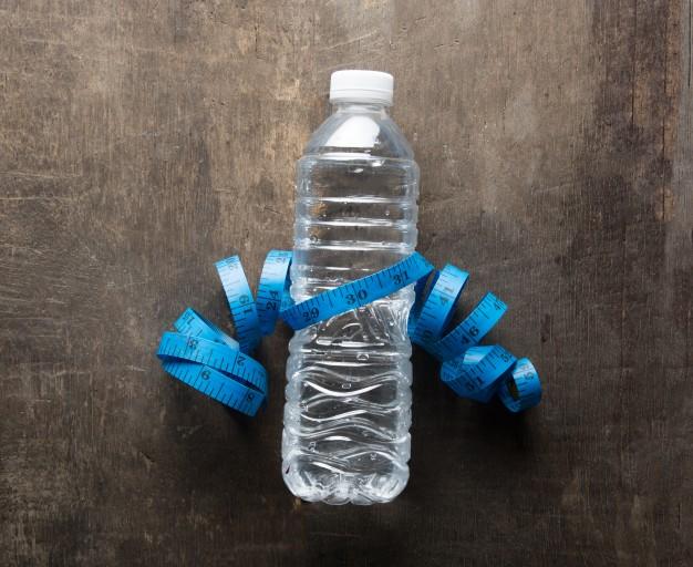 bouteille-d-39-eau-avec-un-ruban-a-mesurer_1150-258